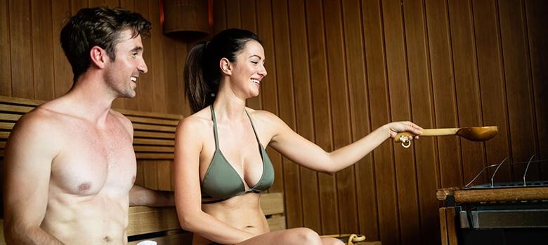 Frau und Mann mit Badekleidung in der Sauna